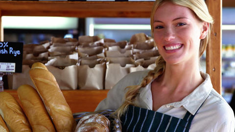 Smiling female staff holding basket of bread at bread counter Footage