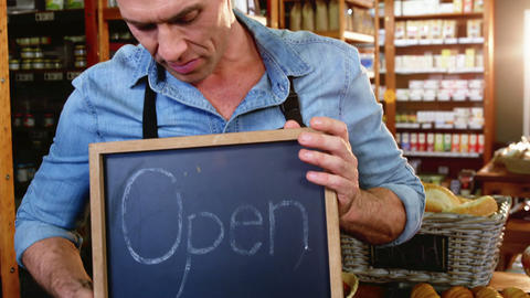 Male staff holding a open sign slate in supermarket, Live Action