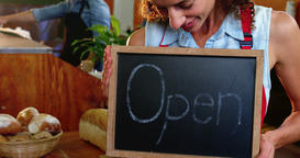 Female staff holding a open sign slate in supermarket Footage