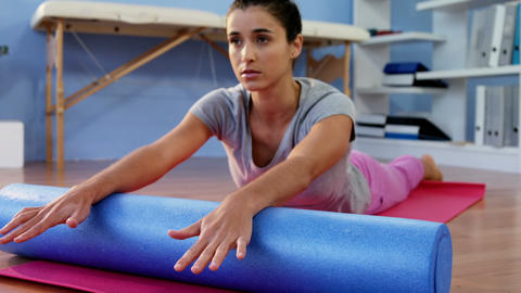 Physiotherapist assisting woman while exercising on exercise mat Footage