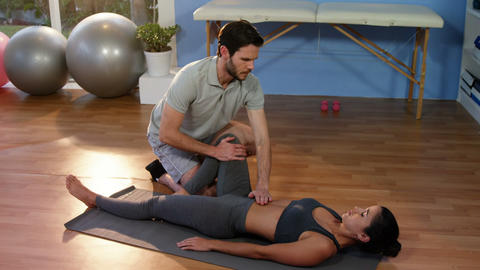 Physiotherapist assisting a female patient while exercising Footage