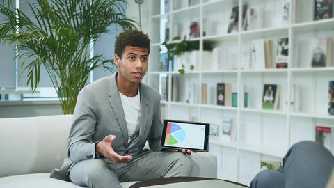 Black formal man making presentation with tablet. Young African-American man in Live Action