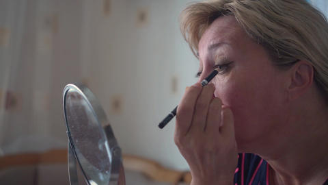 Close up of woman face doing eye makeup with pencil. Adult woman applying pencil Live Action