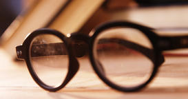 Various books with spectacles on a desk Footage