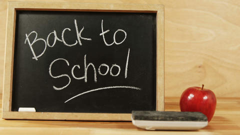 Close-up of chalkboard with blackboard duster and apple Footage