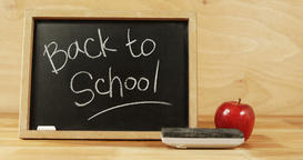 Close-up of chalkboard with blackboard duster and apple Stock Video Footage