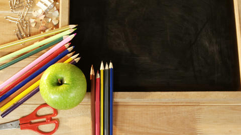 Close-up of chalkboard with colored pencil and apple Footage