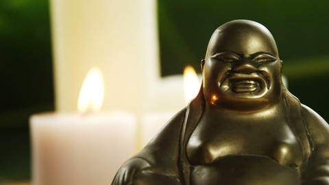 Laughing buddha figurine with burning candles ビデオ