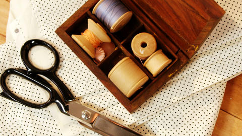 Close-up of thread roll in a box and scissor Footage