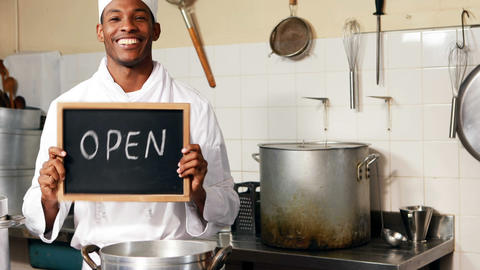 Chef holding showing open sign with chalkboard Live Action
