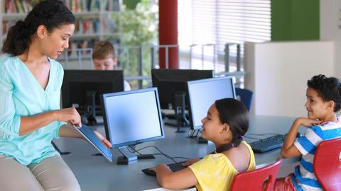Teacher assisting schoolgirls in learning computer Footage