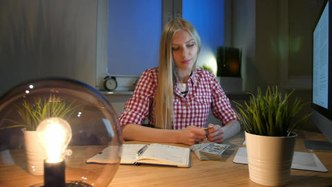 Blond woman at desk looking at bitcoin. Beautiful young blond female sitting at Live Action