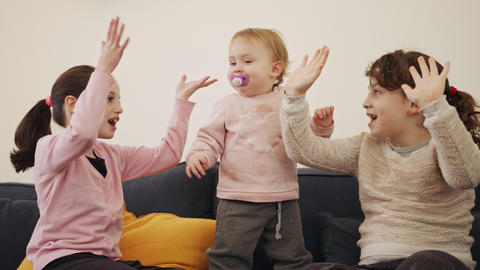 Baby girl playing with 2 young girls, laughing and smiling Live Action