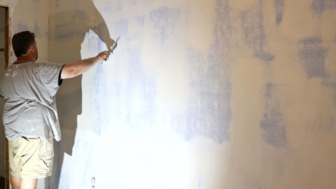 Man putting up a plasterboard a spatula on the white plaster on the wall Live Action