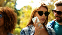 Woman talking on mobile phone with friends in background Live Action