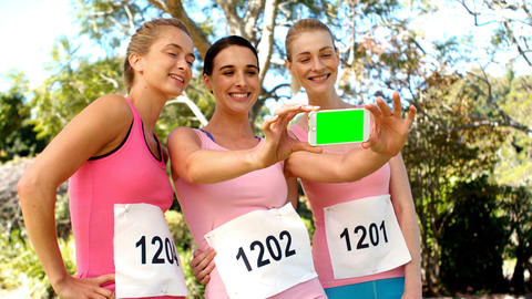 Young female athletes clicking photo from mobile phone Live Action