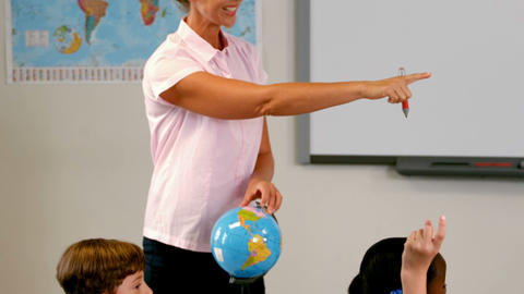Teacher discussing over a globe with kids in classroom Footage