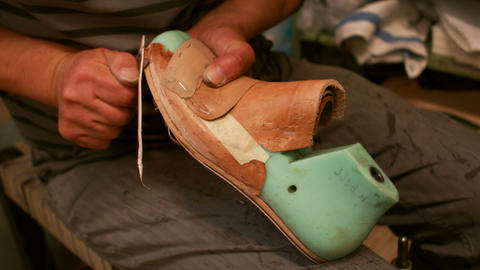 Cobbler cutting a piece of leather on shoe last Live Action