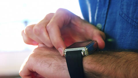 Business executive adjusting a smartwatch Live Action