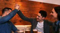 Happy friends giving high five while having a glass of beer Footage