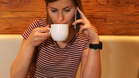 Woman having a coffee while talking on phone Footage