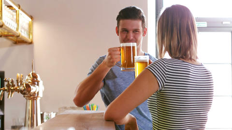 Couple interacting while toasting a glass of beer at bar counter Footage