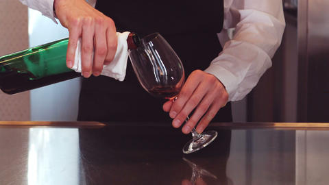 Bar tender pouring red wine in glass Footage