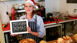 Portrait of waitress showing chalkboard with merry x-mas sign Footage