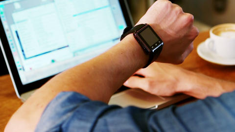 Man checking time on his wristwatch while using laptop Footage