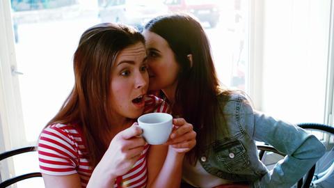 Woman whispering a secret into her friends ear Footage