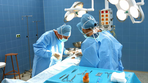 Surgeons performing operation in operation room Live Action