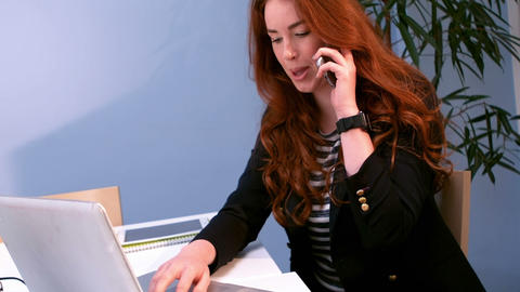 Business executive talking on mobile phone while using laptop Live Action