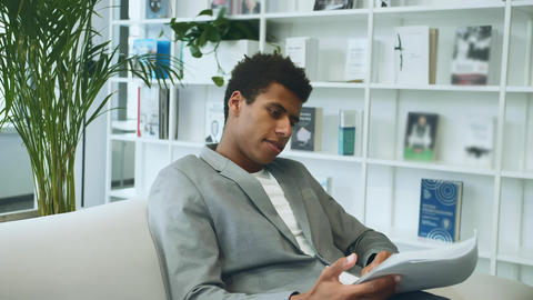 Black businessman reading paper on sofa. Adult African-American man in suit Live Action