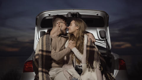 Happy couple rubbing noses sitting in car trunk with beautiful summer twilight Live Action