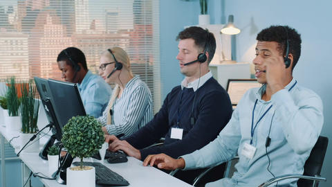Mixed-race customer support operator falling asleep on his table in call center Live Action