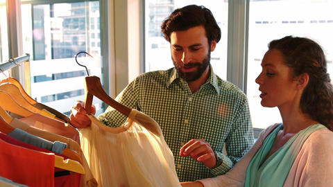 Couple selecting a dress while shopping for clothes Live Action