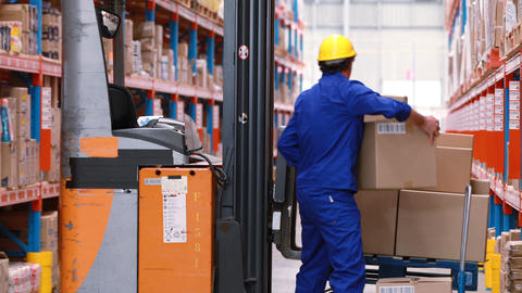 Male warehouse worker arranging stock on forklift truck Live Action