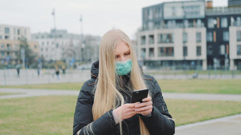 Medium shot of girl wearing medical mask reading outbreaking news about Live Action