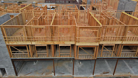 Wooden beam framing on urban apartment complex construction with wooden Live Action