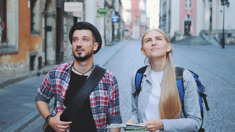 Happy young tourist couple with map walking and looking at old city architecture Live Action