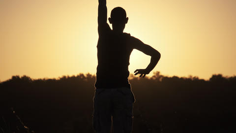 Silhouette of Man against Sunset Raising Hands Up. Freedom. Slow Motion Live Action