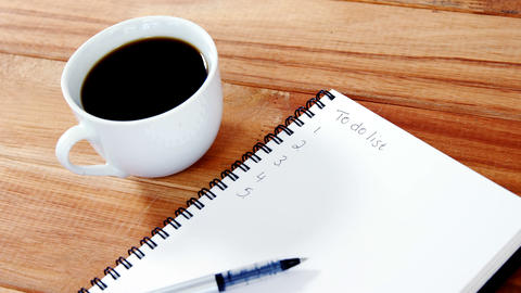 Close-up of coffee cup with diary and pen Footage