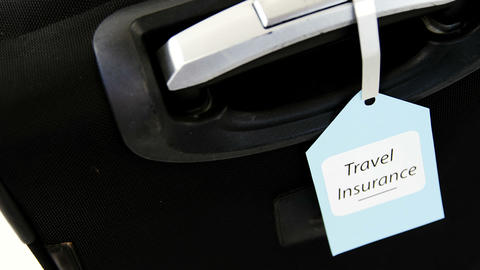 Travel insurance label tied to a suitcase Live Action