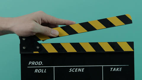 Movie slate. Close up man hand hold empty black and yellow stripe film making clapperboard isolated Live Action