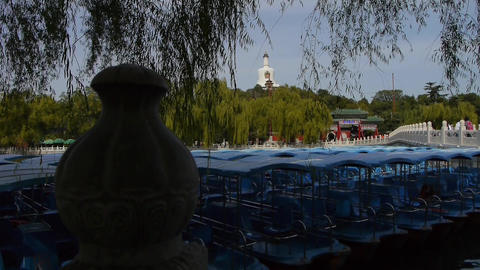a row of blue boats on lake,swing willow in China Beijing Beihai Park Footage