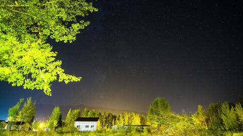Milky Way Timelapse background over village Stock Video Footage