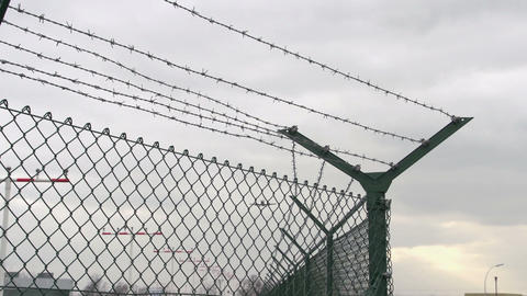 Airplane landing flies over barbed wire Stock Video Footage