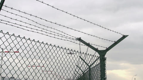Airplane Landing Flies Over Barbed Wire stock footage