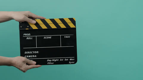 Movie Clapperboard. Film crew man hold and move up film slate in to the frame and clap it Live Action