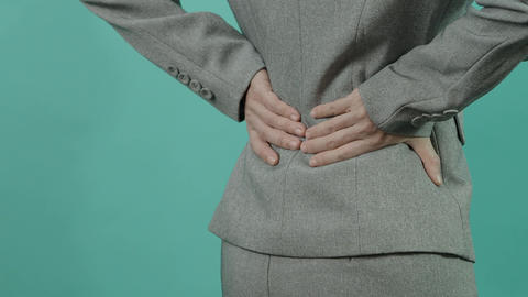 Backache. Lower Back Pain. Unhealthy business woman in working suit touching injured back Live Action